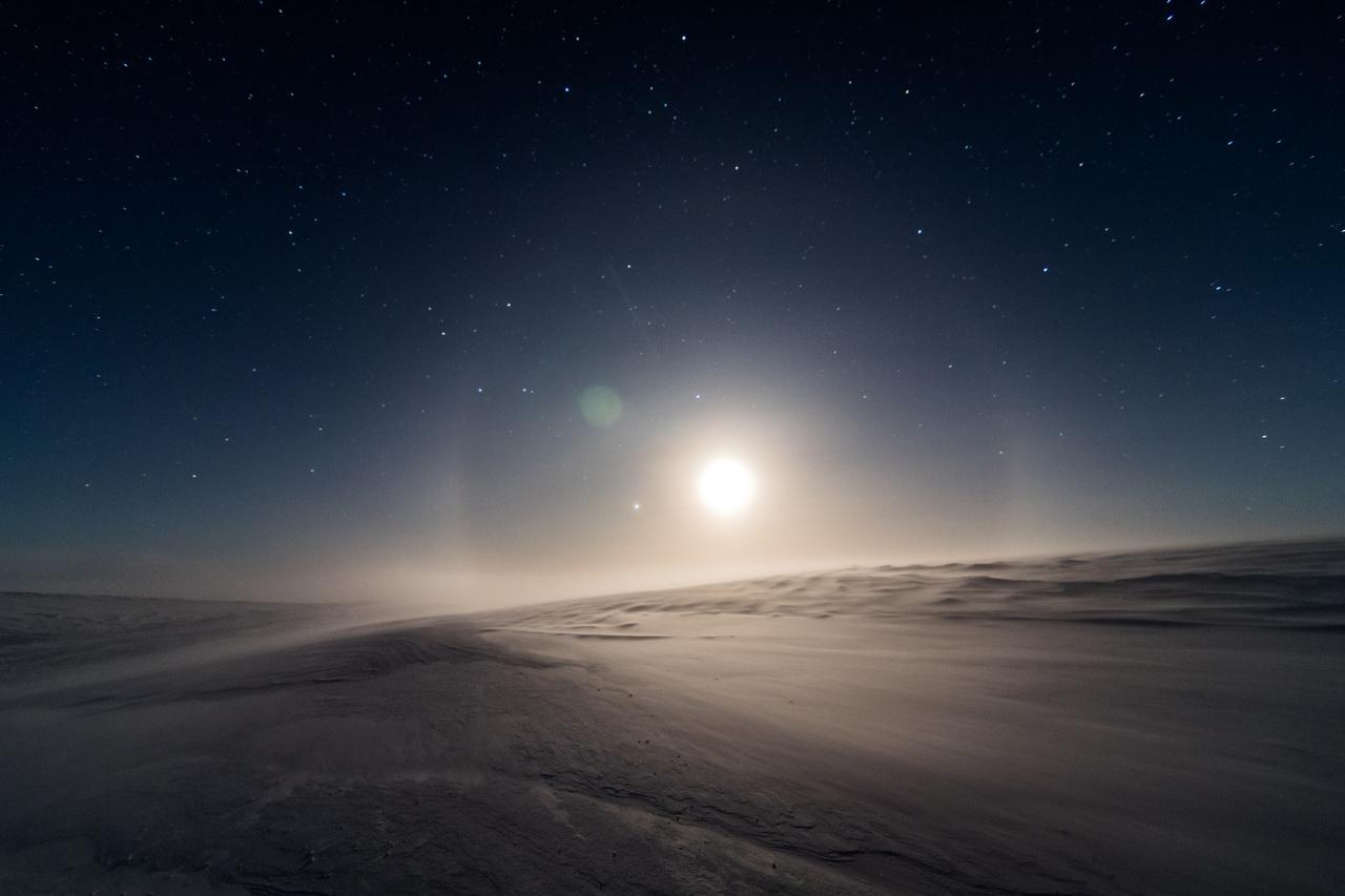 Varázslatos antarktiszi éjszaka, csillagokkal, holdhalóval, sivatagi dűnékhez hasonlatos, szikrázó hótakaróval.