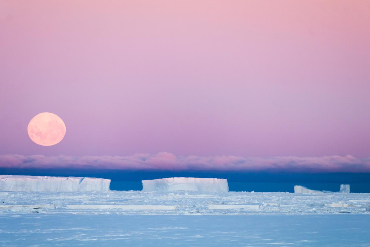 Horizont fölött a légkör torzító hatása miatt kissé összenyomott telihold.