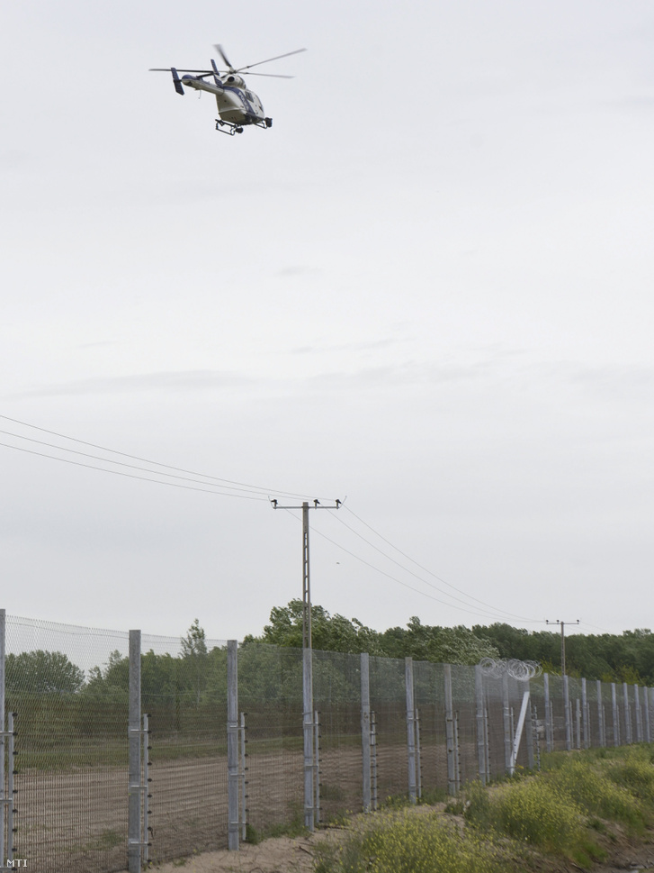 Rendőrségi helikopter repül a szerb-magyar határon álló biztonsági határzár fölött Röszke térségében 2017. április 28-án.