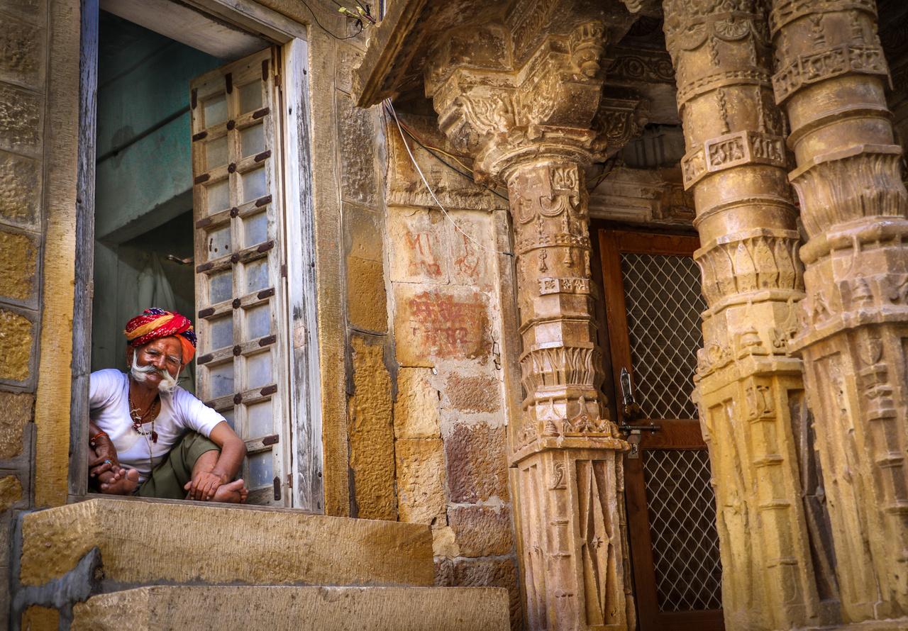 """Dzsaiszalmer egy nagyjából 60 ezer lakosú város Radzsasztánban, a pakisztáni határtól bő száz kilométerre. """"A sivatagból kiemelkedő aranyváros csipkézett homokkő épületeinek köszönheti hírnevét"""", igazi ékkövének a város fölé magasodó, 99 tornyú erődöt szokták nevezni. Gazdagságát kedvező fekvésének köszönhette: az India és Közép-Ázsia között húzódó tevekaraván-útvonalak metszéspontja van itt, így rengeteg kereskedő járt itt, akiket megadóztathattak. A tengeri kereskedelem térnyerése után azonban gyorsan veszített jelentőségéből. A képen látható férfi bajsza azt is megmagyarázza, hogy az indiai léptékkel nézve közeli (bő 300 kilométerre lévő) puskári tevevásáron miért van bajuszszépségverseny is."""