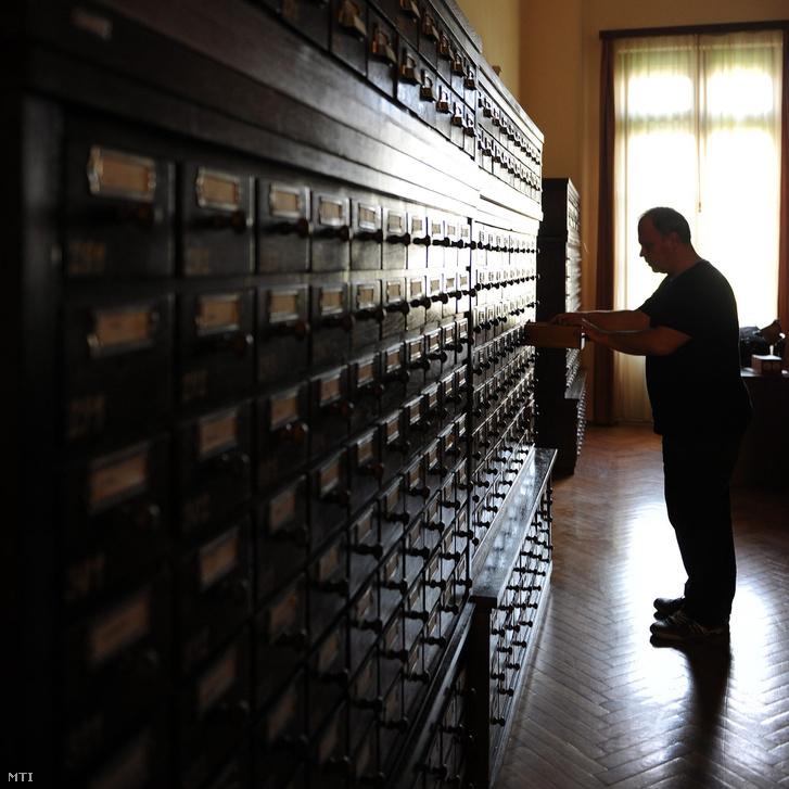 Egy könyvtáros a katalógusszekrény-sornál dolgozik a 100 éves Debreceni Egyetem Egyetemi és Nemzeti Könyvtárban.
