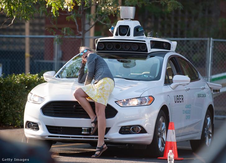 Egy nő pózol az Uber egyik önvezető autójával a cég egyik központjában Pittsburgh-ben