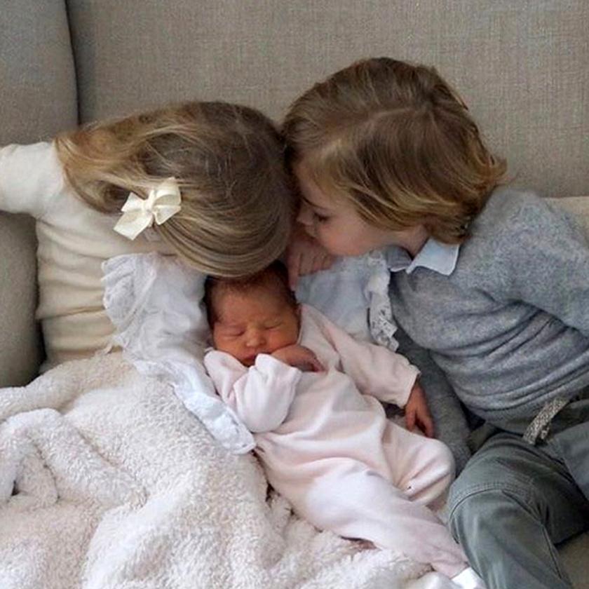 Leonore és Nicolas így puszilják a kishúgukat.