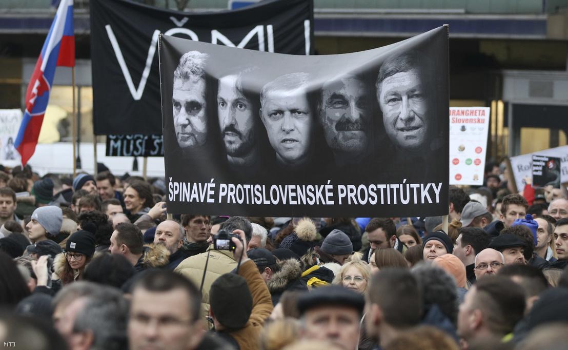 Kormányellenes tüntetés résztvevői mocskos szlovákellenes prostituáltak jelentésű felirattal ellátott, többek között Robert Fico szlovák miniszterelnököt (k) Robert Kalinák belügyminisztert (b2) és Tibor Gaspar rendőrfőnököt (j) ábrázoló transzparenssel Pozsonyban 2018. március 9-én.