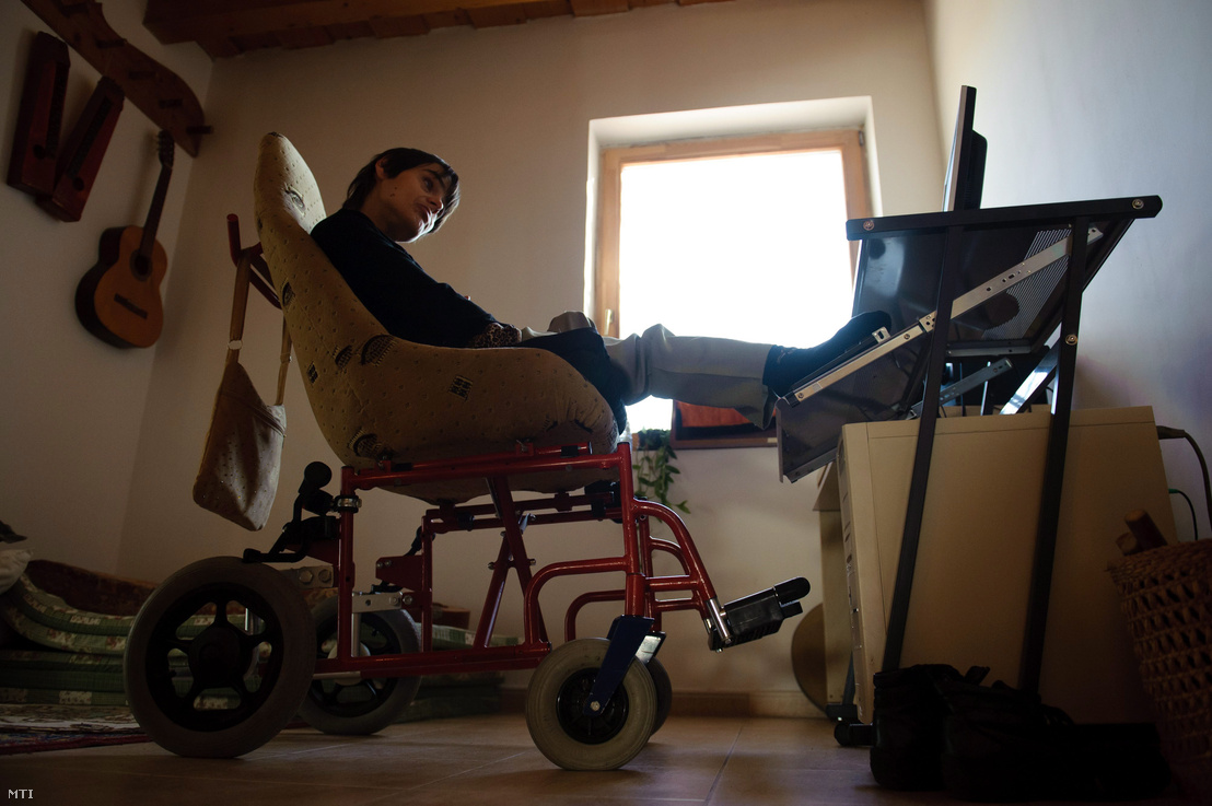 Rosenberger Katalin lábával kezeli a számítógépet a Szederfa Lakóotthonban, Ikladon 2012. november 8-án. Katalin a születésekor fellépő oxigénhiányos állapot következtében lebénult. Nem tudja használni kezeit, beszédét idegenek nem értik meg, de ép értelemmel, mély érzés- és gondolatvilággal éli életét. Lábával kezeli a számítógép speciális billentyűzetét. Újságcikkeket ír a helyi lapba, ő a lakóotthon sajtófelelőse.