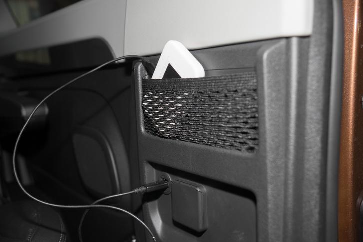 A hátsó USB csak tölt. Mellette egy 230V-os csatlakozó, a fehér tárgy pedig egy mobil router a teljes mobilitásért. Egyes modellekben ezért több százezer forintot kérnének el.