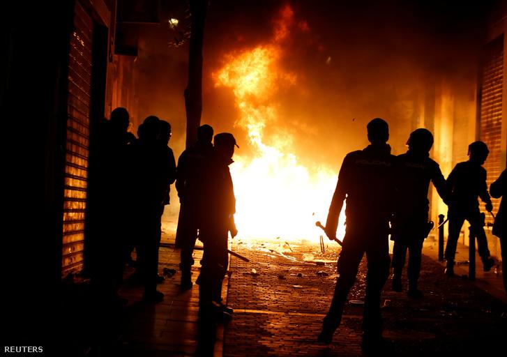 Felgyújtott szemetesek előtt álló rendőrök Madrid központjában március 15-én éjjel