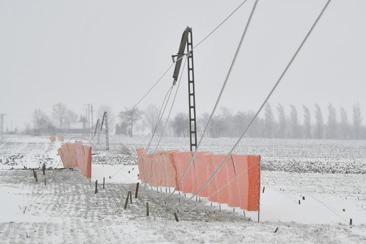 A hóviharral járó erős szél miatt kettétört villanypóznák a 33-as főút mellett Debrecen határában.