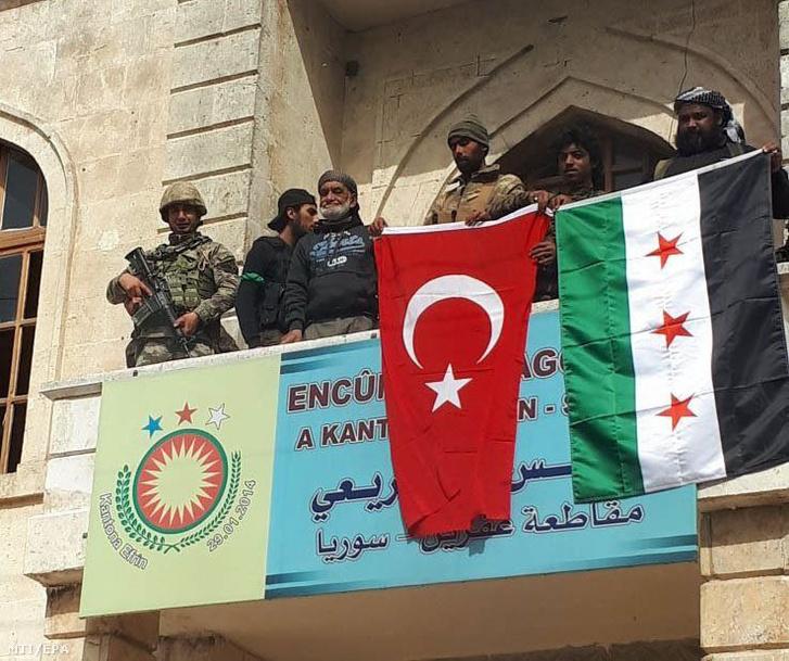 A török és a szíriai zászlót tartják katonák egy kurd kormányzati épület erkélyén az észak-szíriai Afrínban 2018. március 18-án, amikor Recep Tayyip Erdogan török elnök bejelentette, hogy a török katonasággal együttműködő szíriai csapatok teljes mértékben visszavették a várost a kurd milíciáktól.