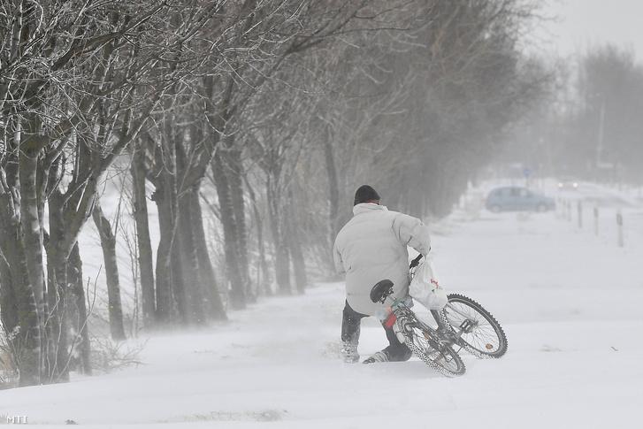 Egy férfi tolja kerékpárját a hófúvásban a Hajdúnánás és Hajdúdorog közötti úton 2018. március 18-án.