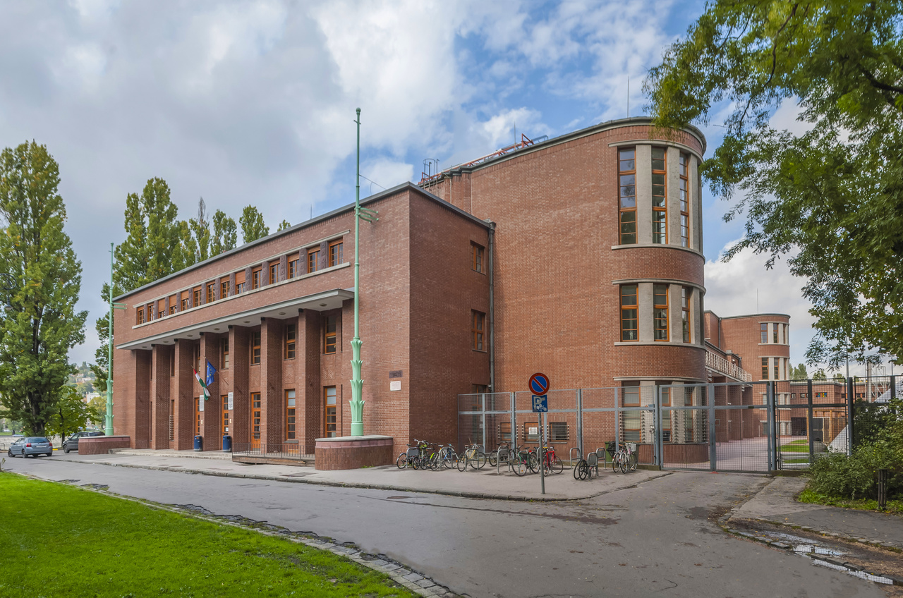 18. Margitsziget, Nemzeti Sportuszoda, Hajós Alfréd, 1929–1930                         Hajós tehetséges építész, úszó olimpikon és a labdarúgás szervezője volt; végül a harmadik tervváltozata valósulhatott meg. Először konzervatívabb homlokzatú épületet tervezett, míg a második verzióban az uszoda belül egyiptomi oszlopokkal rendelkezett. Igényesen kivitelezett épület, amely máig megőrizte eredeti részleteit. Az elülső két, félhengeres épületrész a tribünökhöz vezető lépcsőházat rejti. A bejárat fölötti ablakok között klinker terrakotta díszítmények láthatók, a zászlótartó rudak lépcsőzetes pálmalevél-kompozícióból indulnak ki. Hajós 1924-ben indult az olimpiai játékok művészeti versenyében, így naprakész volt a nemzetközi sportépítészetben. A bejárat kialakítására hatott az amszterdami Olimpiai Stadion (Jan Wils, 1927–1928) amelyet Frank Lloyd Wright elpusztult chicagói Midway Gardense (1913–1914) is inspirált.