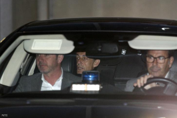 Nicolas Sarkozy volt francia elnök (k) elhagyja a Párizs melletti Nanterre korrupcióellenes hivatalát 2018. március 21-án, a második napi kihallgatásának végén.