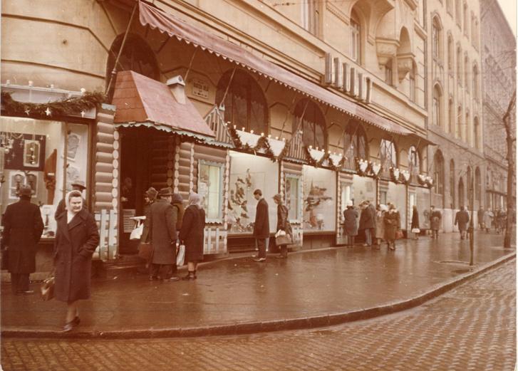 A Bartók Béla utcai Szivárvány Áruház kínálatát bemutató kirakatai és bejárata látható az éppen vásárló emberekkel.