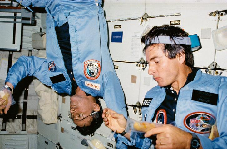 Young (balra) az 1983-as STS-9 űrsiklóküldetésen étkezés közben, mellette társa, a német Ulf Merbold