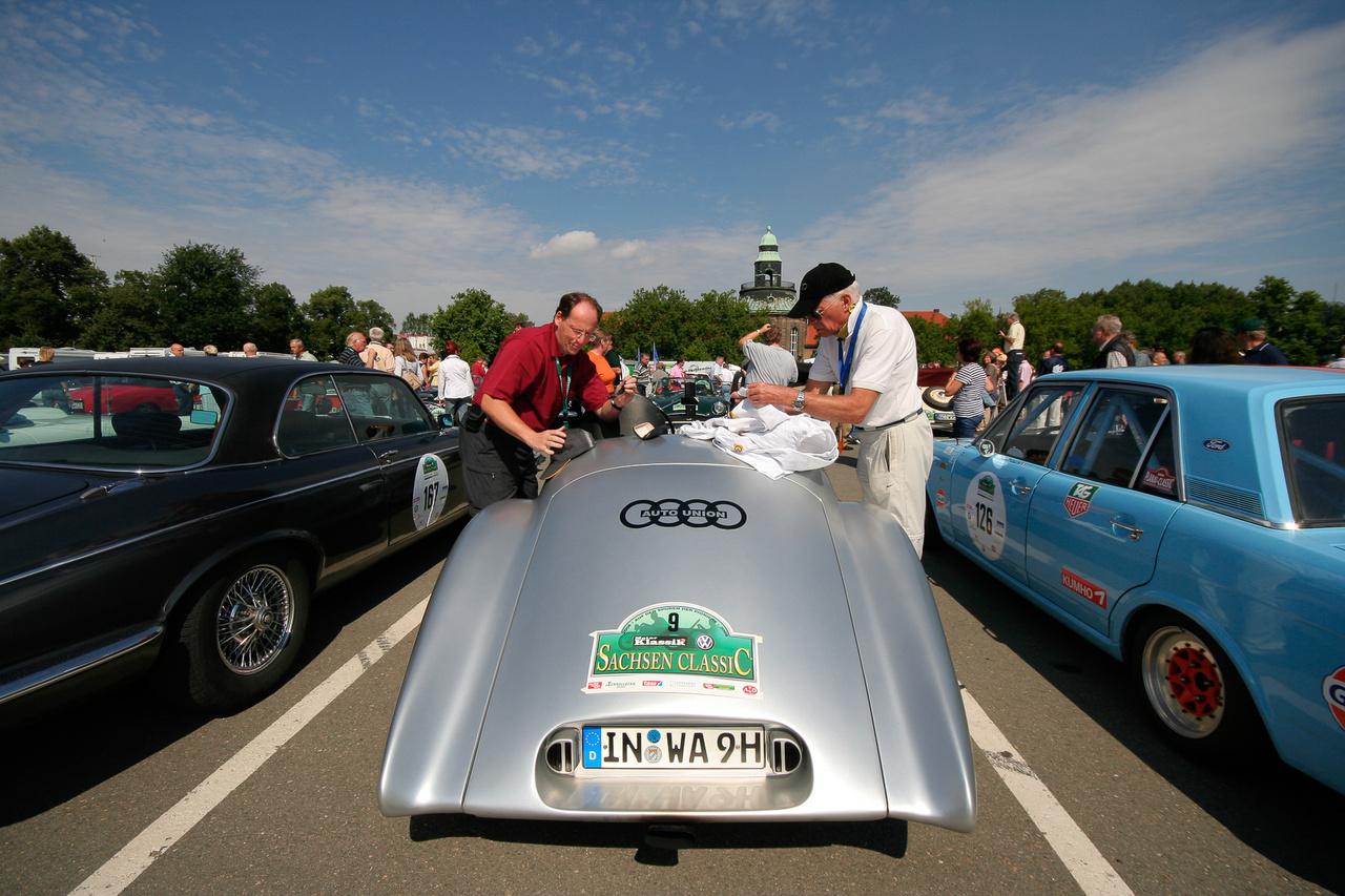 A fefér ruhás bácsi az utáníéptett Auto Uniontól jobbra Bernd Rosemeyer unokája. A nagypapa ilyennel versenyzett