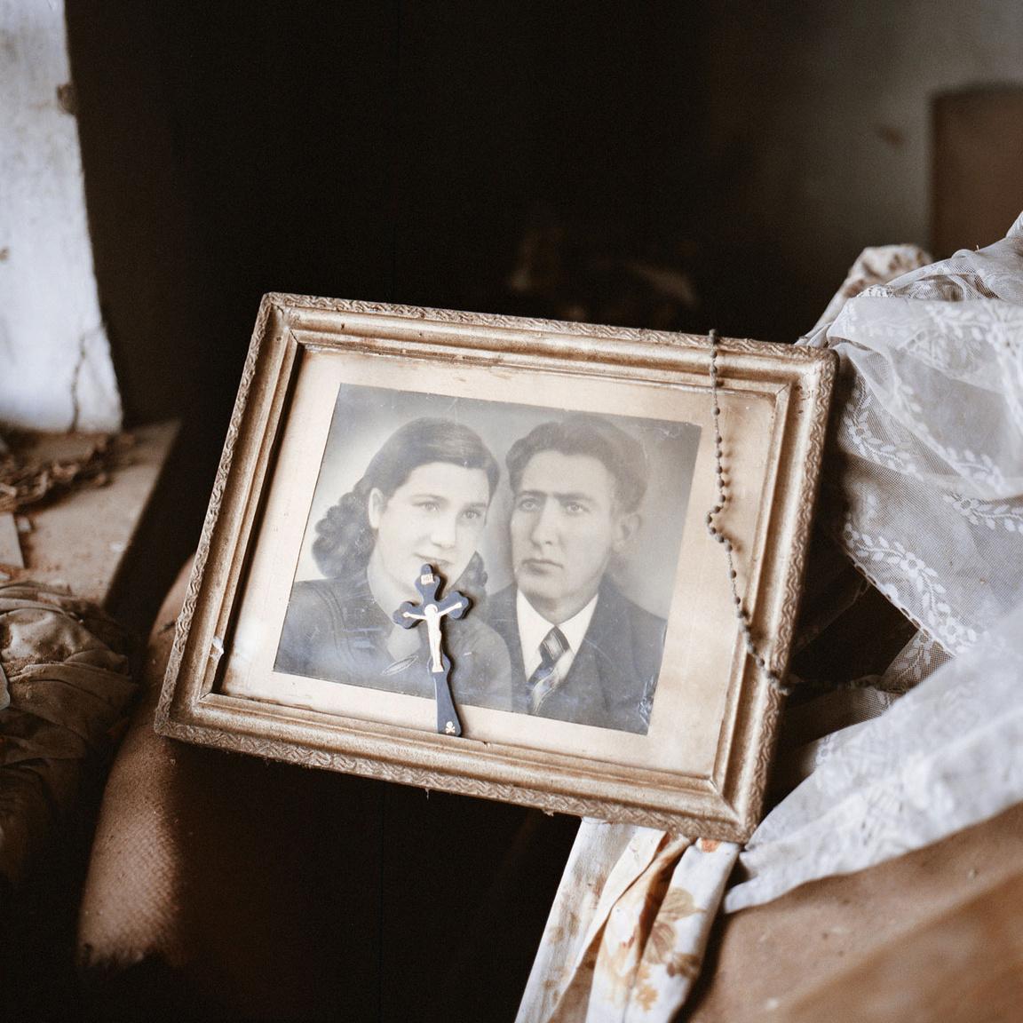 Házaspár portréja kereszttel és rózsafüzérrel egy üresen álló házból.