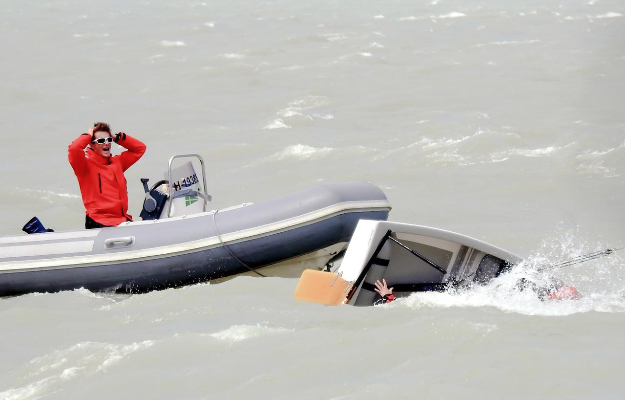 """Török Brigitta: Havaria a Balatonon // """"Ez a kép a Balatonon készült az egyik Optimist versenyen. Nagyon erős szél volt, hatalmas lökésekkel, a képen látható kislány már ötödszörre borult fel hajójával egymás után, óriási kitartással és küzdelemmel mindig egyedül állította vissza hajóját és próbált kijutni a partra, edzője arcán az 5. borulás """"ezt nem hiszem el"""" kifejezés látható."""""""