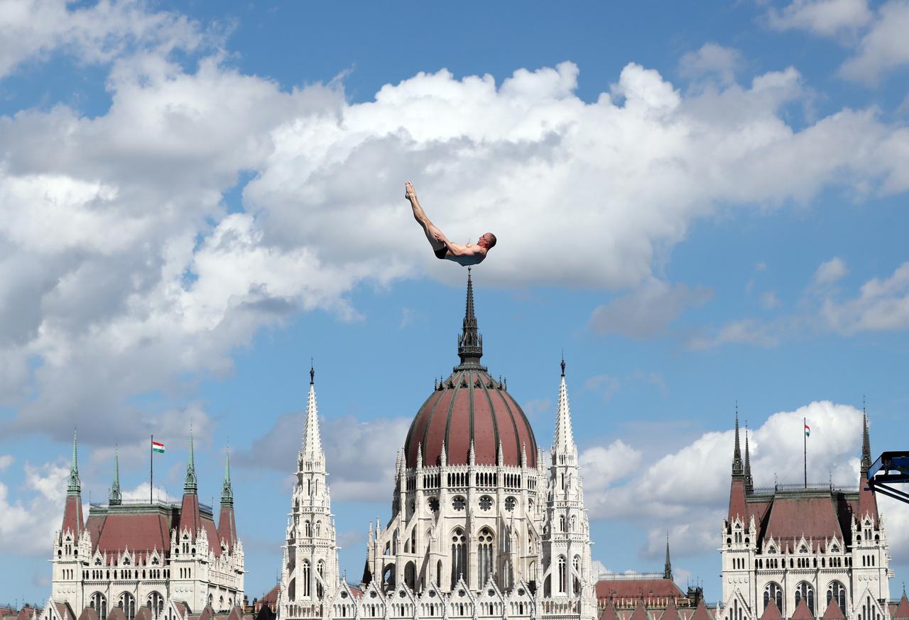 """Szaka József: Csúcs ez az érzés! // """"A Budapesten rendezett 17. FINA világbajnokságon, a férfi toronyugrás versenyén, 2017. július 28.-án, az orosz Igor Semashko ugrása közben. A versenyzők 27 méter magasból, közel 100 km/órás sebességet elérve ugrottak a Dunában kialakított, medencébe. Az Országház kitűnő háttere volt, az amúgy is bámulatos látványnak. Az ugró egyfajta csúcsdíszként tetszeleg a Parlament kupolájának tetején."""""""