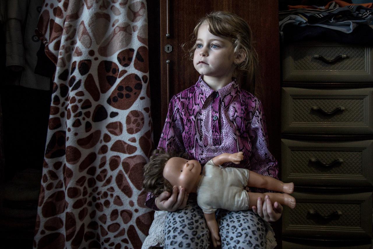 """Szöllősi Mátyás: Egy árva házról (sorozat) /  A négy éves Nórika a babájával. // """"A beregszászi Gagarin utca egyik házában ötvennégy család él: magyarok, romák, ukránok együtt, súlyos körülmények között. A ház egykor a helyi varroda épülete, annak kollégiuma volt, majd az államosítás után hajléktalanok költöztek be egy időre, végül az önkormányzat más, rászoruló családoknak adta bérbe a helyiségeket. A házban fűtés, illetve vízszolgáltatás nincs, és tető is csak nemrég került rá. A lakók helyzete - mind a ház állapota, mind az önkormányzattal kötött bizonytalan bérleti szerződések miatt - meglehetősen kétes. A ház jól példázza a Kárpátalján kialakult szociális helyzetet, és azt, hogy miért vándorolnak el az emberek tömegével Beregszászról és környékéről. A sorozat 2017 őszén készült."""""""