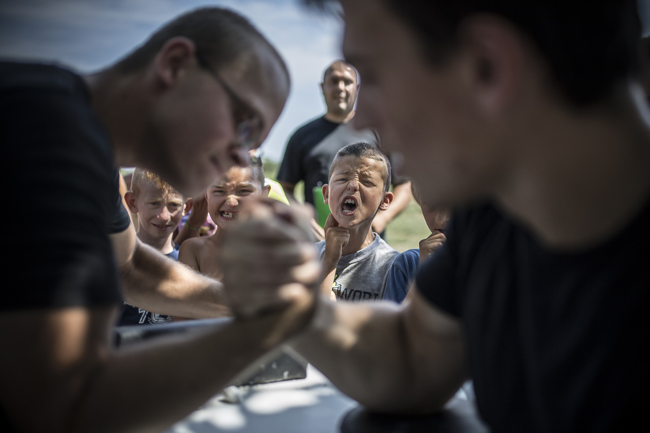 """Hajdú D. András: Úgy lenyomlak ballal, hogy becsinálsz! (sorozat) / A verseny további célja, hogy a kallódó gyerekeknek programot biztosítsanak a nyár közepén, illetve hogy az izmos szkanderosok példáján a fiatalok is kedvet kapjanak a testedzéshez, ami az iskolai teljesítményükre is kihat. // """"Kadarkúton a Dózsa utca egyike a kisváros szegregátumainak. A Máltai Szeretetszolgálat hat éve van jelen a szinte kizárólag romák által lakott utcában, ahol tanodát üzemeltetnek, és mindenféle programmal próbálják bevonzani környék fiataljait. A szegregátumban havonta rendeznek erős ember versenyt, ami roppantul népszerű a telepiek között, akik verítékben fürödve igyekeznek szkanderban vagy éppen kocsihúzásban felülkerekedni a többieken.                         A verseny további célja, hogy a kallódó gyerekeknek programot biztosítsanak a nyár közepén, illetve hogy az izmos szkanderosok példáján a fiatalok is kedvet kapjanak a testedzéshez, ami az iskolai teljesítményükre is kihat."""""""