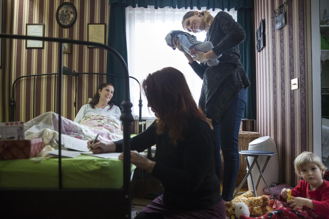 """Pályi Zsófia: Otthon született! // """"Oláh Orsolya budapesti otthonában fekszik, azon az ágyon, ahol második gyermekét is világra hozta. Zajlik körülötte az élet, nővére csodálja az újszülöttet, nagyobbik kislánya pedig a földönjátszik, mindezalatt Béres Edina bába a kötelező adminisztrációt írja."""""""