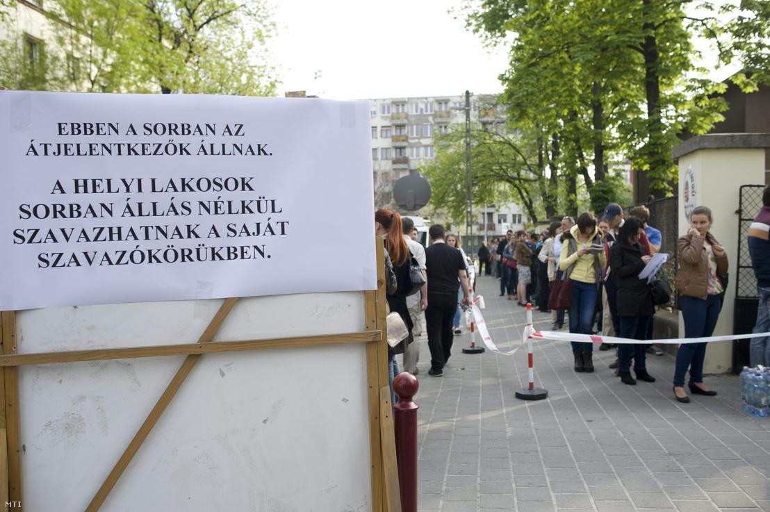 Átjelentkezők állnak sorba a Bocskai út és Nagyszőlős utca sarkánál az újbudai Bocskai István Általános Iskola épületében kialakított 35-ös számú szavazókör előtt az iskola udvarán este 19 óra után az országgyűlési képviselő-választáson 2014. április 6-án.