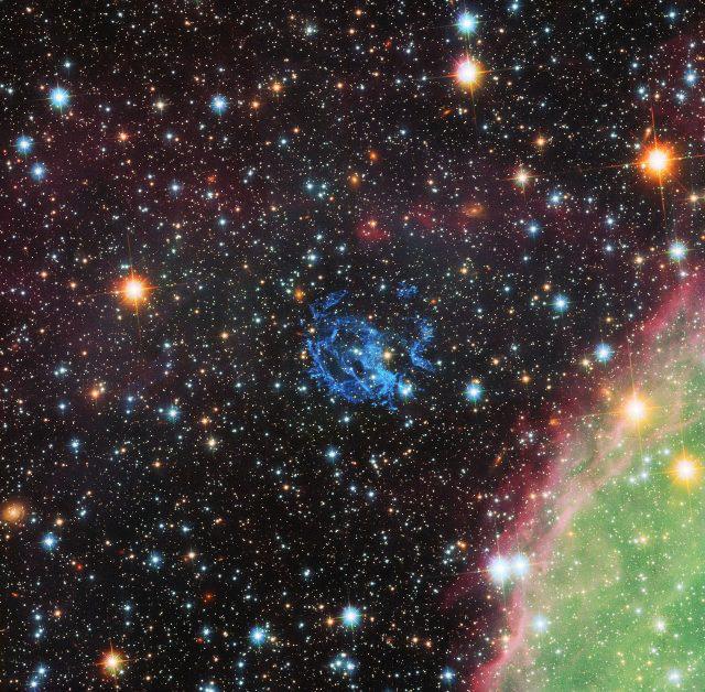 A NASA/ESA Hubble-űrtávcsöve által készített képen az 1E 0102.2-7219 jelű szupernóva-maradványt alkotó csomók kék színben láthatók a kép közepének közelében. A kép jobb alsó sarkában zöldben és rózsaszínben az N 76 vagy Henize 1956 katalógusjelű hatalmas csillagkeletkezési terület egy része is megfigyelhető.