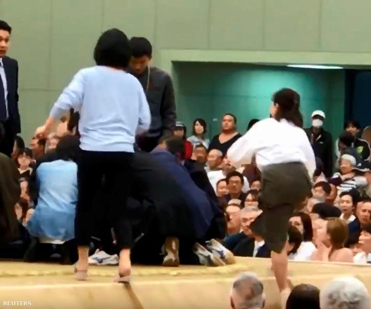 Egy nő próbál fellépni a küzdőtérre, hogy ellássa a beszéde közben összeesett Riozo Tatamit