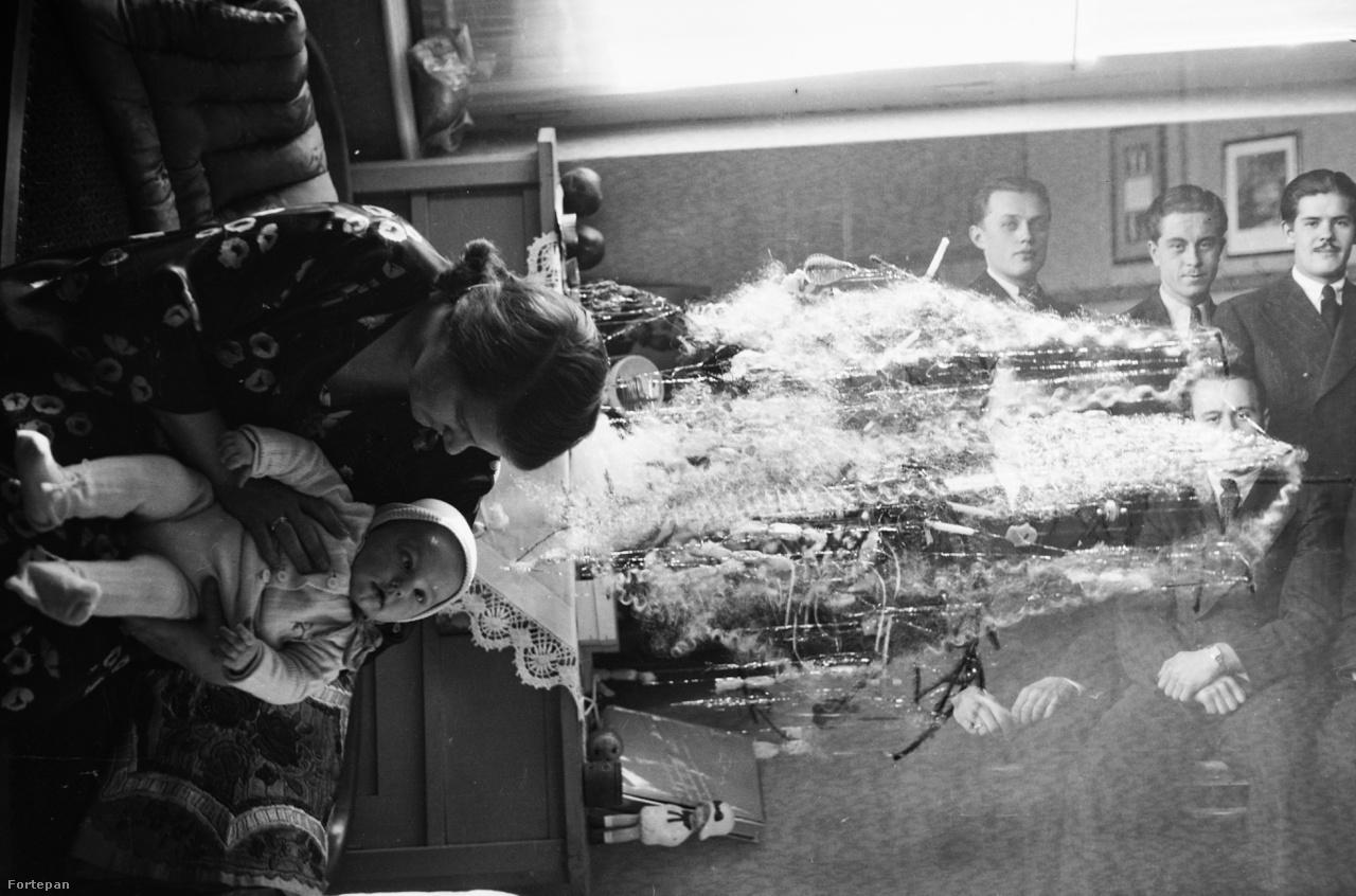 A gazdagon díszített karácsonyfa ezen az 1936-os bakin elsőre egy művészi torzításnak vagy satírozásnak tűnik. A fa alá került férfi csoportkép tiszteletre méltó tagjaiból pedig csak néhány szerencsésnek sikerült rákerülnie a fotóra. A bandzsító kisbaba arckifejezése pontosan tükrözi azt, amit ennek a képnek a láttán érezhet a műértő. A kor két világa, az otthon gyereket nevelő nő és a klubban networkölő férfiak sose kerülhettek volna egy képre, ha nincs az a fránya kettős expó.