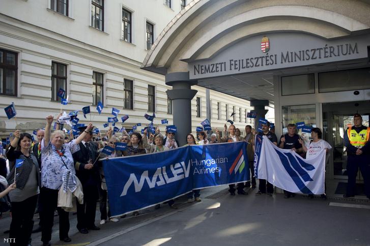 Résztvevők a HUNALPA Magyar Közforgalmú Pilóták Egyesülete és a Malév Munkavállalók Érdekvédelmi Szervezetei demonstrációján a Nemzeti Fejlesztési Minisztérium épülete előtt Budapesten 2014. március 29-én.