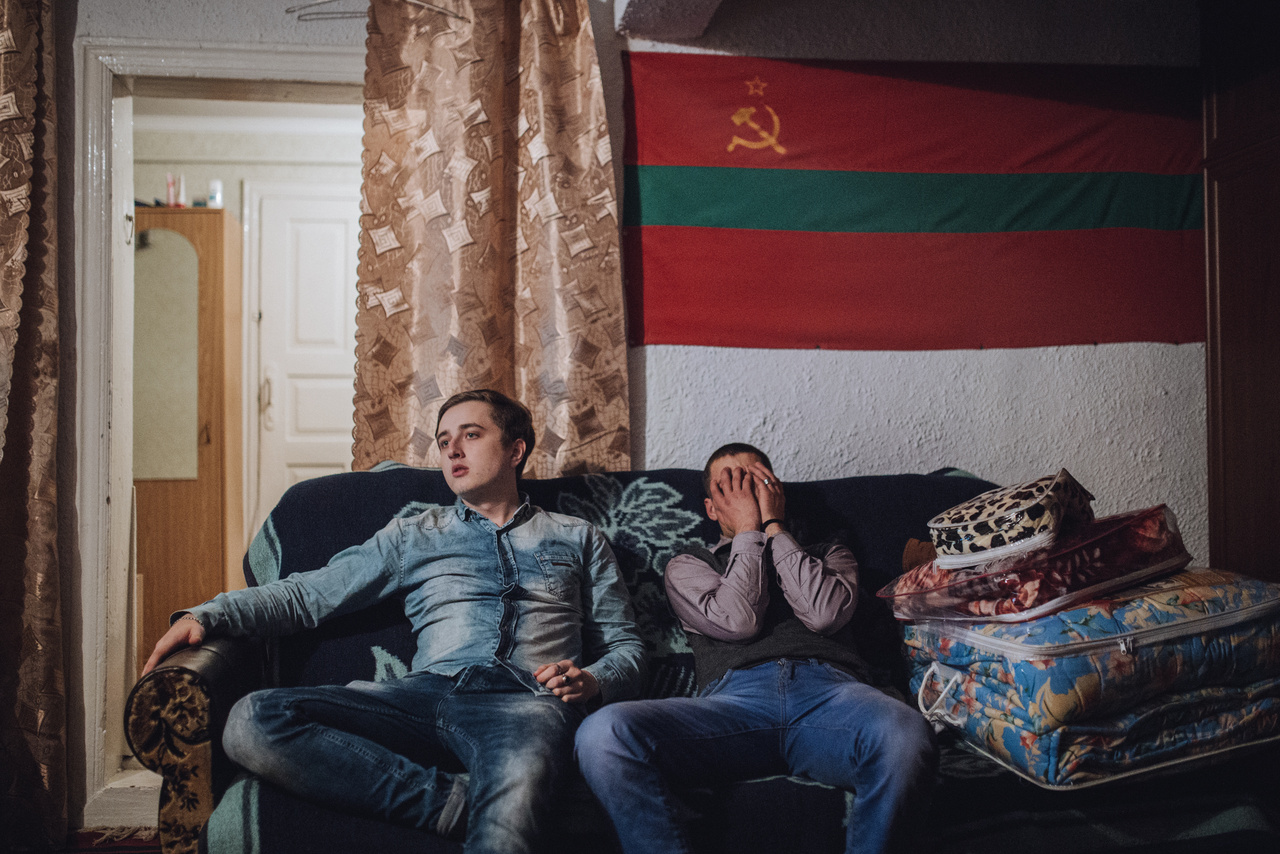 Aljosa és Jura a PMR zászlaja alatt. A szakadár állam az egykori Moldáv SZSZK zászlaját vette át, ezzel is hangsúlyozva a Szovjetunióhoz kötődő múltat. Még a sarló-kalapácsot is megőrizték.