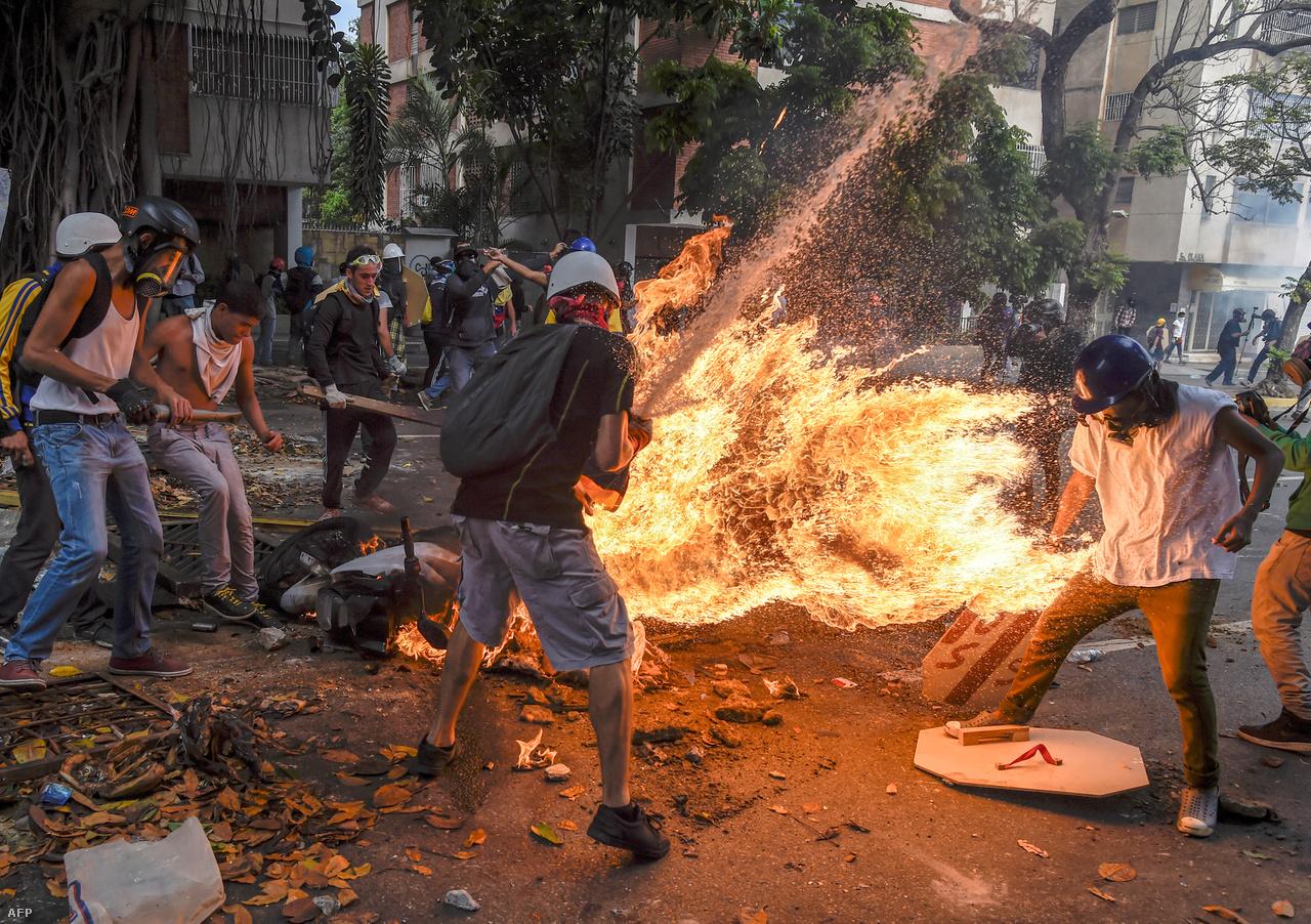 Juan Barreto hír kategóriában (sorozat) harmadik helyezett képe is Caracasba repít minket, az utcai zavarásokba torkolló, Maduro-ellenes tüntetés helyszínére. A képen egy kigyulladt és belobbanó rendőrmotort állnak körül tüntetők, miközben egyiküket a felcsapó lángok megpörkölik.