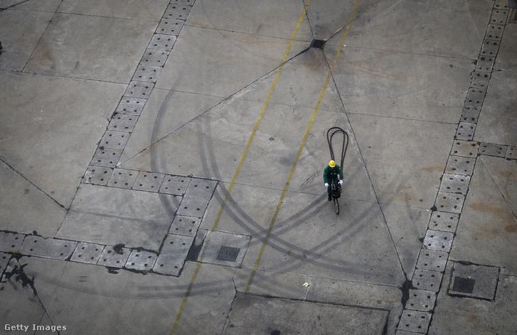 Munkás kerékpározik a MOL százhalombattai üzemében
