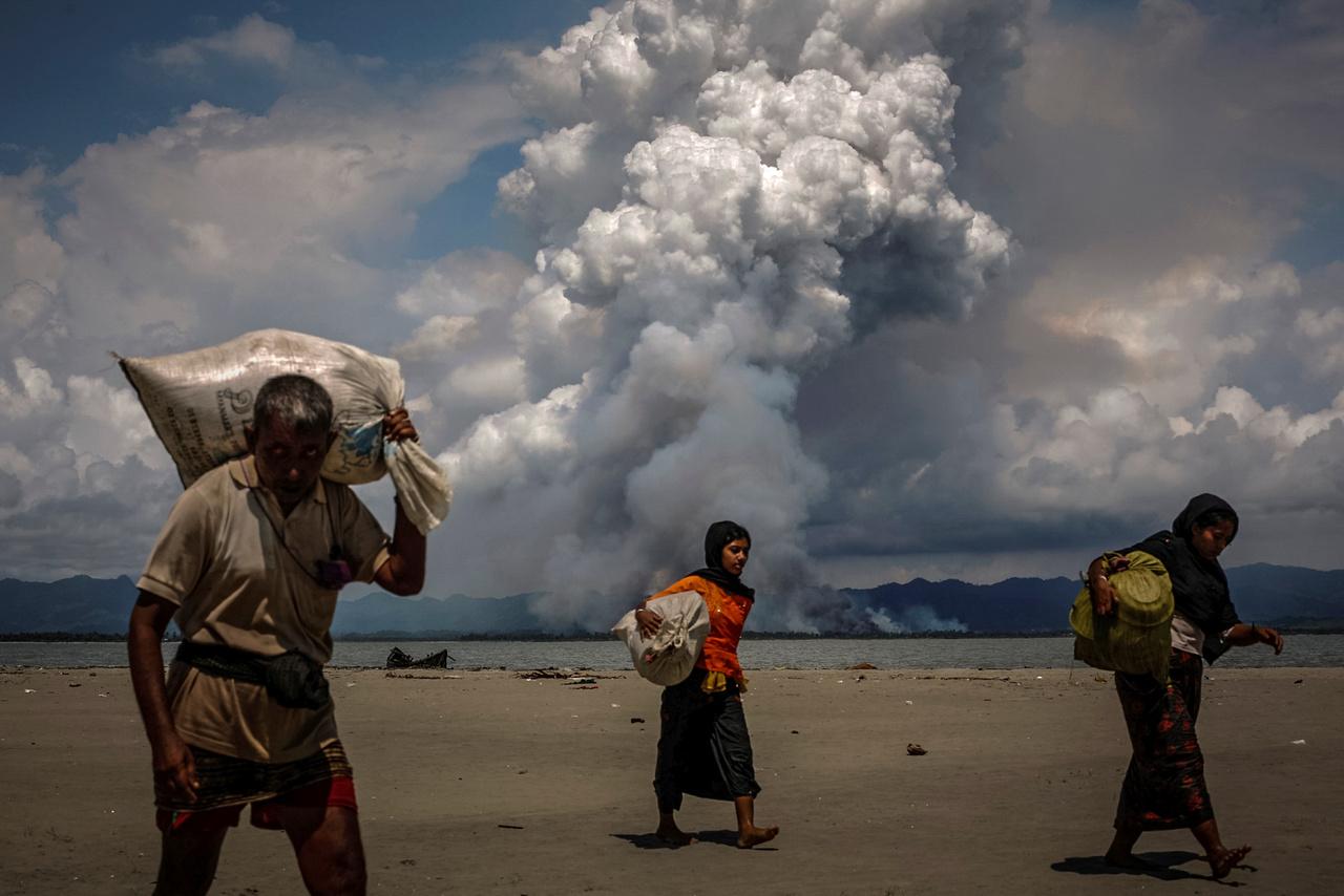 Lángoló terület füstje látszik a mianmari partok felől, miközben a vízen átkelt menekültek sétálnak a túlsó parton a bengáli öbölben.