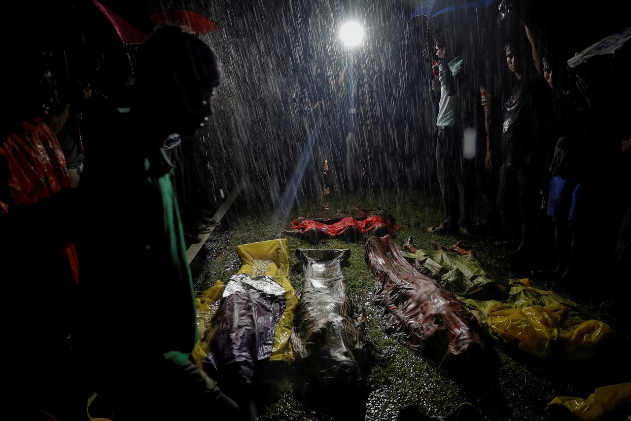Hajótörés áldozatai - a vízből frissen kiemelt holttestek hevernek a parton Inaninál, miközben sűrű eső esik egy este.