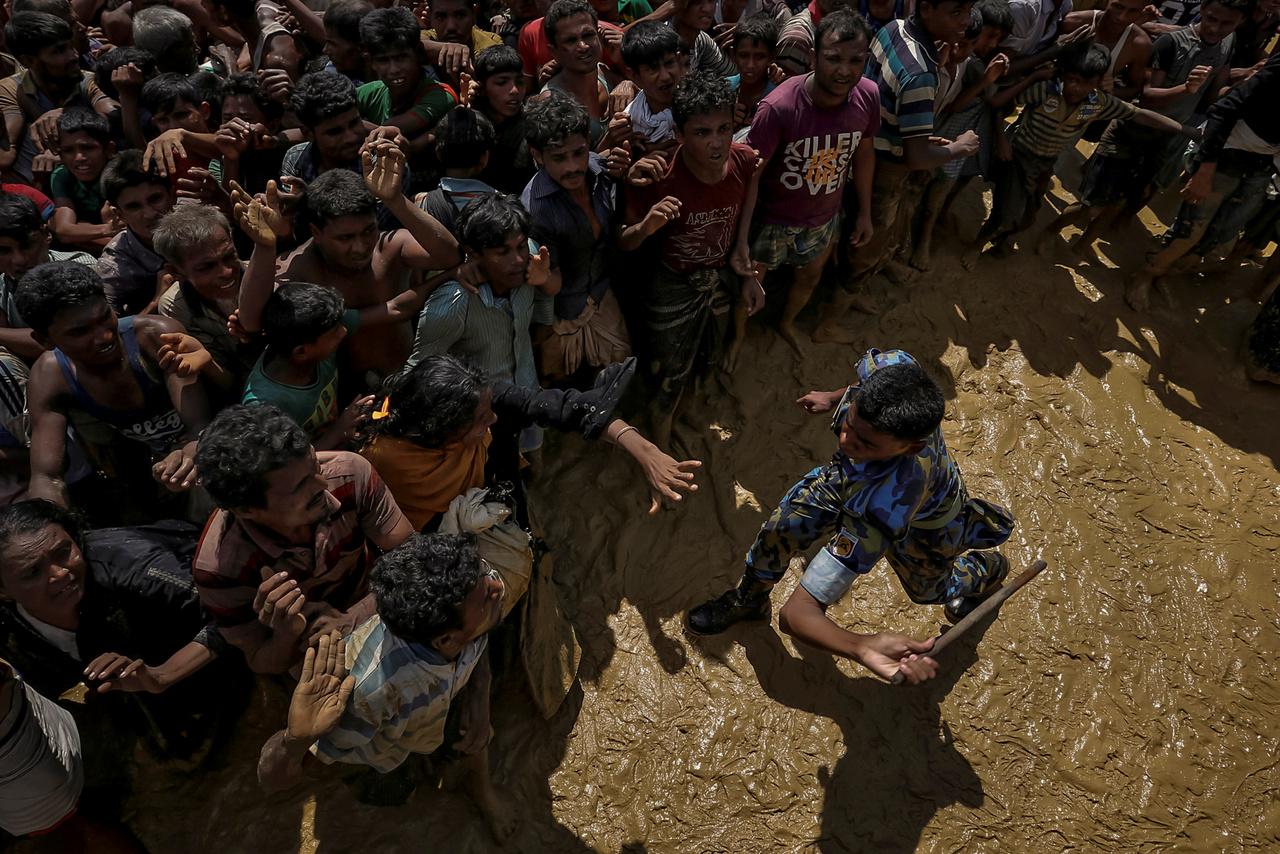 Segítségre váró menekülteket próbál visszatartani egy rendőr egy Banglades melletti gyűjtőpontnál.