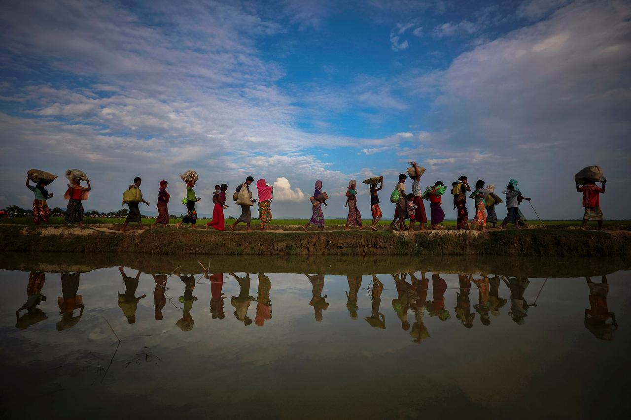 Menekültek sétálnak egy töltésen Palang Khali-felé, Banglades mellett.