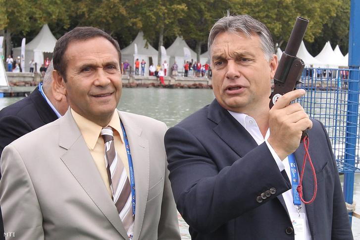 Orbán Viktor miniszterelnök rajtpisztollyal elindítja a nők 7.5 kilométeres versenyét a junior nyíltvízi úszó-világbajnokságon, Balatonfüreden 2014. szeptember 6-án. Mellette Gyárfás Tamás, a Magyar Úszó Szövetség elnöke.