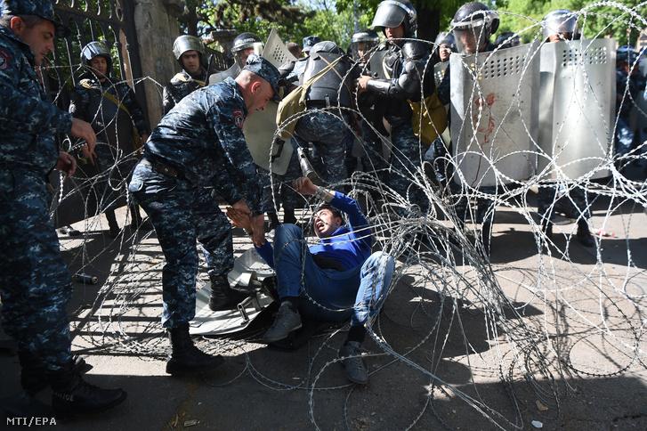 Pengésdrót közé esett tüntetőt segít fel egy rendőr a Szerzs Szargszján korábbi köztársasági elnök miniszterelnökké választását ellenző tiltakozáson Jerevánban 2018. április 16-án, egy nappal az előtt, hogy a jereváni törvényhozás kormányfőt választ.