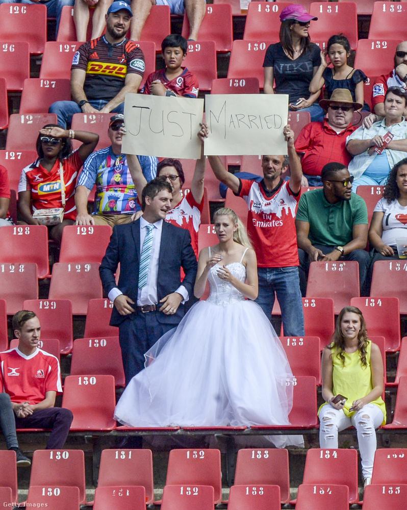 És gondolhatnánk, hogy ők csak úgy poénból öltöztek be a meccsre, de a mögöttük ülők által feltartott táblák azt mondják, hogy tényleg friss házasokról van szó, akik szemlátomást egyenesen a házasságkötésről jöttek ki a meccsre.