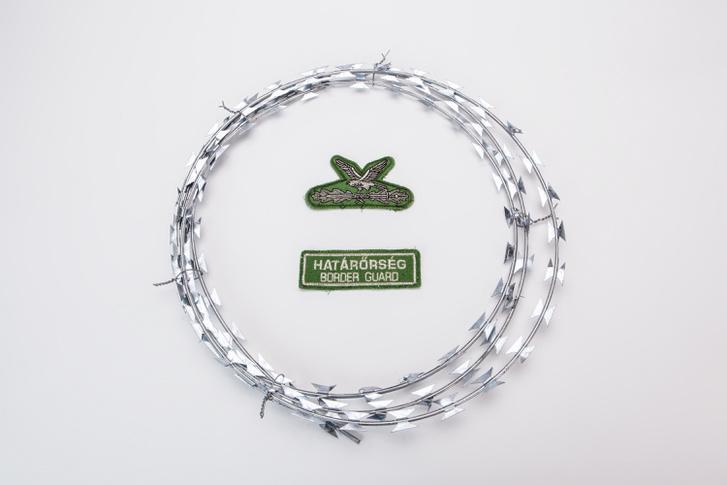 """Drótkerítés-darab (20. sz.) A kiállítási felirat: """"A NATO szögesdrót (katonai megnevezéssel GYODA – gyorstelepítésű drótakadály), alkalmas térbeli objektumok megvédésére a nem kívánt betolakodókkal szemben"""". Középen a határőrök turulos felvarrója."""