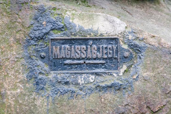 A Velencei-hegységben Nadapon a szintezési õsjegy 1888-ban felállított emlékműve mögötti függőleges sziklafalfelületre elhelyezett MAGASSÁGJEGY jelzés illetve a szöveg alatti vízszintes vonal a tényleges magasság megjelölése.