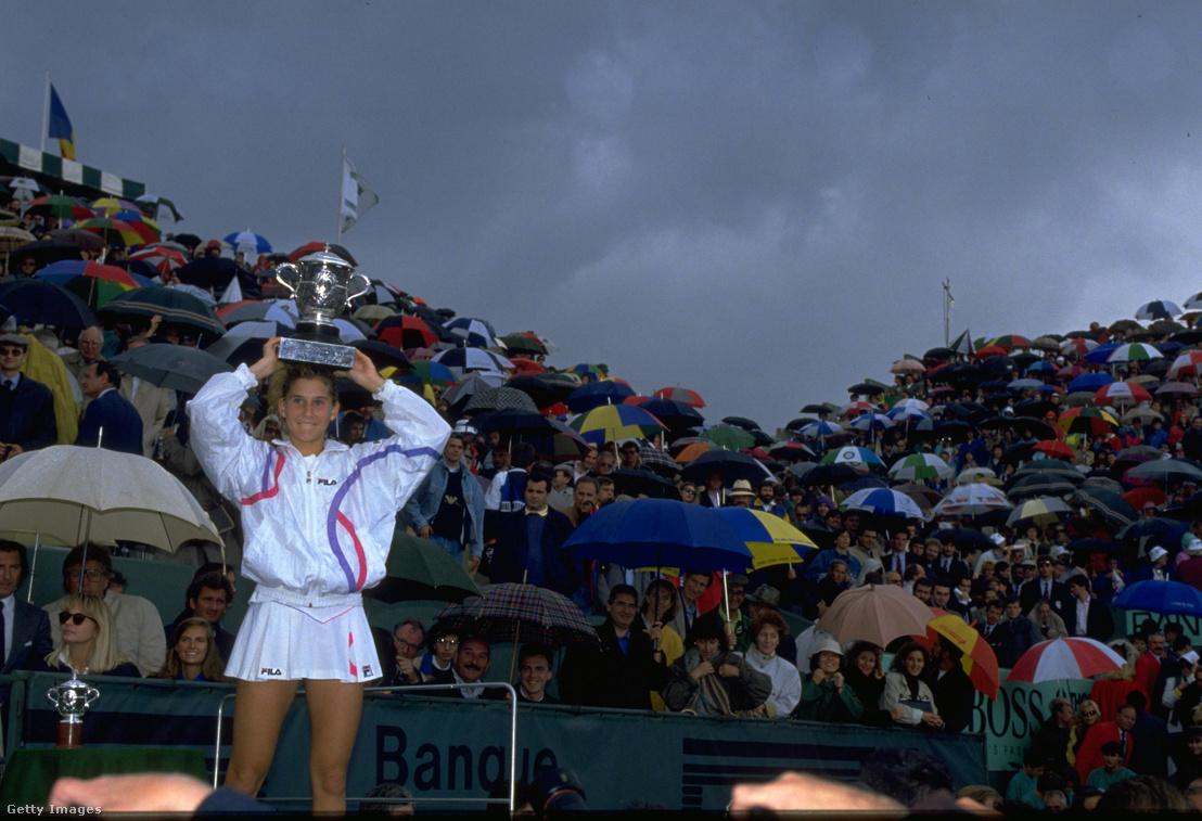 Szeles Mónika trófeájával védi magát az esőtől, miután a francia nemzetközi nyílt teniszbajnokság döntőjében legyőzte Steffi Grafot.