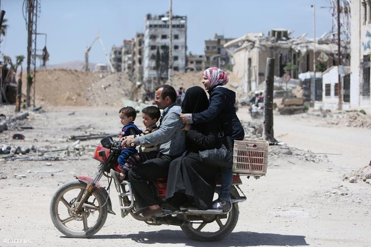 Robogón közlekedik egy szíriai család Dúma lebombázott városrészében, április 16-án.