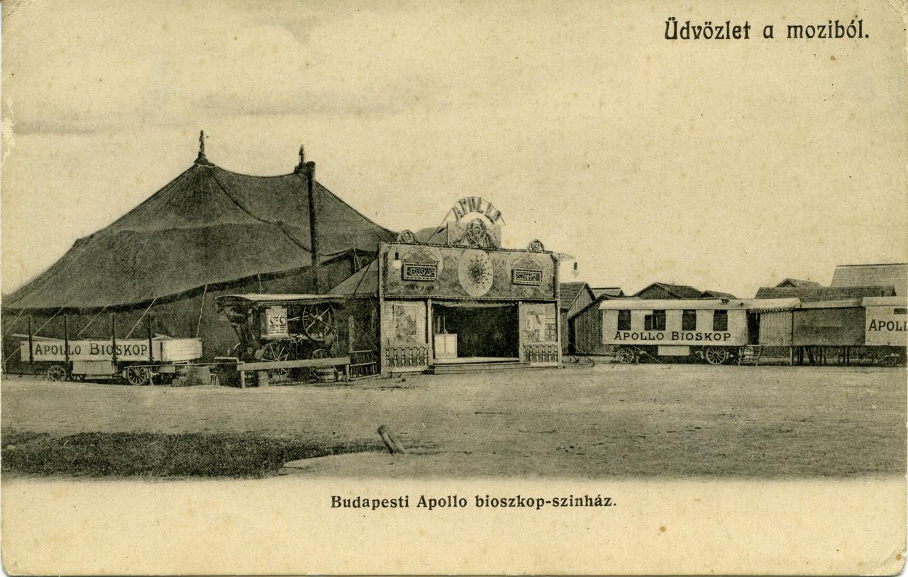 A helyszín sajnos ismeretlen, a látvány azonban lenyűgöző, hiszen az egyik első magyar mozit láthatjuk az 1900 körüli képeslapon. A pesti városhatáron felvert hatalmas sátor egy úgynevezett vándormozi volt, amelynek tulaja a háttérben veszteglő kocsijaival járta az ország búcsúit, vásárait. A sátor előtt felállított hatalmas gőz-cséplőgép a vetítéshez szükséges villanyáramot állította elő, a díszesre pingált bejárat előtt pedig kikiáltó verbuválta a sokadalom bámészkodóit. Az előadás alatt ugyanez az ember hosszú pálcával a kezében a vászon előtt magyarázta a közönségnek a filmek tartalmát. Ez a szakma a stand-up comedy őse volt, melynek népszerűségére jellemző, hogy a közönség egy idő után már nem csak a film, hanem a pálcás magyarázó szövege miatt is lelkes híve lett mozinak.