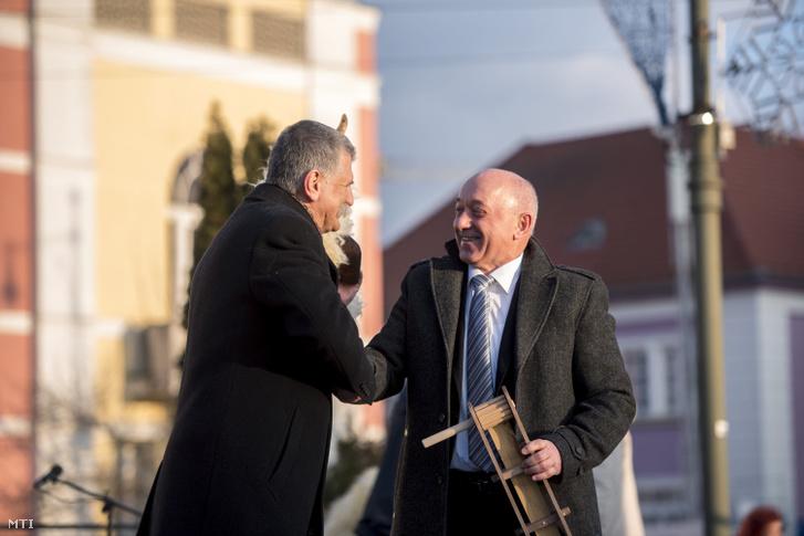 Szekó József Mohács polgármestere (j) egy busómaszkot és egy kereplőt ad át Kövér Lászlónak az Országgyűlés elnökének a mohácsi busójárás negyedik napján 2018. február 11-én.
