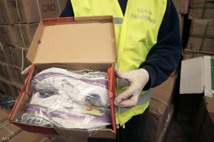 Képünk illusztráció (A Vám- és Pénzügyőrség Országos Parancsnokságának munkatársa egy pár hamis Nike edzőcipőt tart a kezében, 2008)