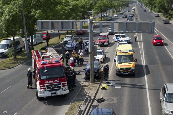 Tűzoltók, rendőrök és mentők dolgoznak egy összeroncsolódott személyautó mellett az Üllői út és a ferihegyi gyorsforgalmi út találkozásánál 2018. április 30-án. Az autó oszlopnak hajtott, a járművet vezető idős férfi a helyszínen meghalt.