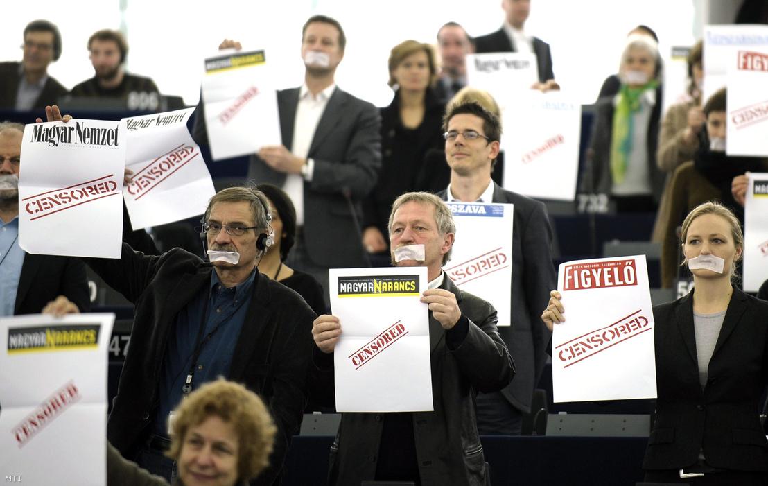"""Leragasztott szájú EP-képviselők """"Cenzúrázott"""" feliratú újságcímlapokat emelnek a magasba Orbán Viktor magyar kormányfő beszéde közben az Európai Parlament (EP) plenáris ülésén Strasbourgban 2011. január 19-én. A miniszterelnök a soros magyar EU-elnökség munkaprogramját ismertette."""