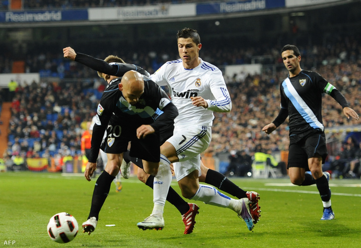Cristiano Ronaldo párharca a Malaga védőjével Manolo Gasparal, háttérben Fernando Fernandez érkezik a Spanyol Bajnokság mérkőzésén 2011. március 3-án Madridban.